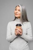 Asijská žena v roláku s šedými vlasy drží kávu jít izolované na šedé