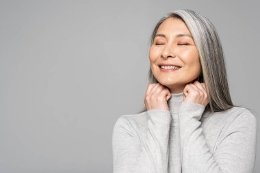 happy asian woman in turtleneck with grey hair and closed eyes isolated on grey