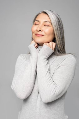 smiling asian woman in turtleneck with grey hair and closed eyes isolated on grey
