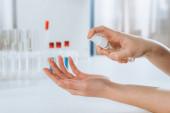 Fotografie Ausgeschnittene Ansicht eines Arztes, der in der Nähe von Reagenzgläsern Antiseptikum auf die Hände sprüht