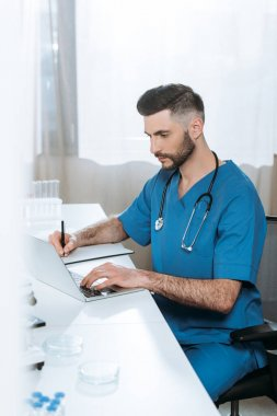 Selective focus of attentive doctor writing while typing on laptop stock vector