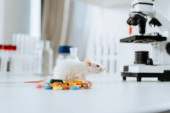 selektiver Fokus der weißen Maus in der Nähe von Kapseln und Mikroskop auf dem Schreibtisch