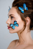 attractive woman with blue decorative butterflies on face isolated on grey