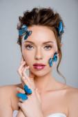 atraktivní žena s modrými dekorativními motýly na obličeji při pohledu do kamery izolované na šedé