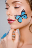 attractive woman with closed eyes and blue decorative butterflies on face isolated on grey