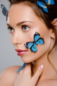 selective focus of young woman with blue decorative butterflies on face isolated on grey