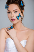 atraktivní mladá žena s modrými dekorativními motýly na tváři izolované na šedé