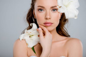 Fotografie white blooming flowers near beautiful woman touching face isolated on grey