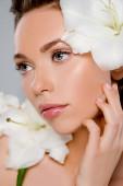 selektivní zaměření bílých kvetoucích květin v blízkosti atraktivní žena dotýkat tvář izolované na šedé