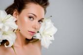 junge attraktive Frau in der Nähe von weiß blühenden Blumen isoliert auf grau