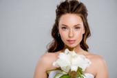 mladá krásná žena dívá na kameru v blízkosti bílého květu izolované na šedé
