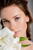 csinos nő nézi kamera közelében fehér virágok