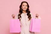 boldog fiatal nő gazdaság bevásárló táskák elszigetelt rózsaszín