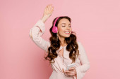 cheerful girl with closed eyes listening music in wireless headphones and holding smartphone on pink