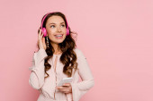 Photo happy girl listening music in wireless headphones and holding smartphone isolated on pink