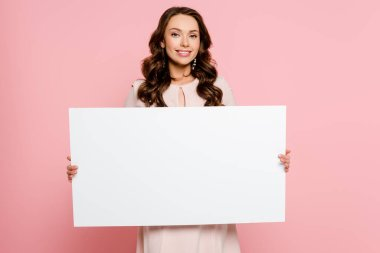 Cheerful young woman holding empty placard isolated on pink stock vector