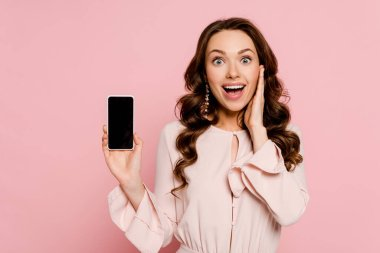 Excited girl holding smartphone with blank screen and looking at camera isolated on pink stock vector