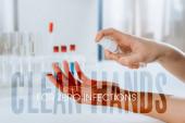 Fotografie Ausgeschnittene Ansicht eines Arztes, der antiseptische Mittel auf Hände in der Nähe von Reagenzgläsern sprüht, saubere Hände für null Infektionen Illustration