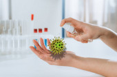 Fotografie Ausgeschnittene Ansicht eines Arztes, der antiseptische Mittel auf Hände in der Nähe von Reagenzgläsern sprüht, Bakterien-Illustration