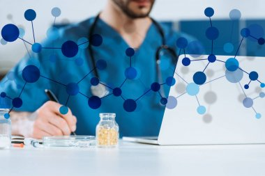 Selective focus of young doctor writing near laptop and container with medicines, molecule structure illustration stock vector