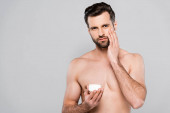 bez košile muž drží kontejner při aplikaci kosmetické krém izolované na šedé