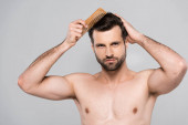 muscular and bearded man brushing hair isolated on grey