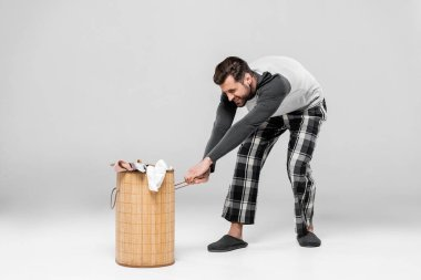 Emotional man pulling heavy laundry basket with dirty clothing on grey stock vector