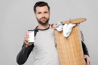 KYIV, UKRAINE - MARCH 23, 2020: handsome man holding laundry basket and smartphone with apple music app on screen isolated on grey