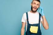 Aufgeregter Reiniger in Uniform und Gummihandschuhen mit Teppich am Smartphone