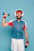 glücklicher stylischer Sportler im Kopfhörer, der mit Hanteln auf blauem Hintergrund trainiert