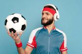 šťastný stylový sportovec ve sluchátkách s fotbalovým míčem na modrém pozadí