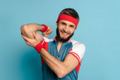 Photo smiling stylish sportsman touching biceps on blue background