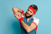 Photo stylish sportsman looking at biceps on blue background