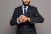 cropped view of bearded businessman in suit looking at wristwatch on grey background