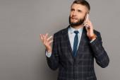 pohledný vousatý podnikatel v obleku mluvit na smartphone na šedém pozadí