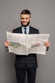 usmívající se pohledný vousatý podnikatel v obleku čtení novin na šedém pozadí