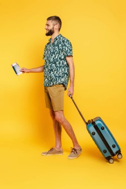 Full length view of happy bearded guy with travel bag and passport on yellow stock vector