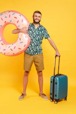 Full length view of happy bearded guy with travel bag and swim ring on yellow stock vector