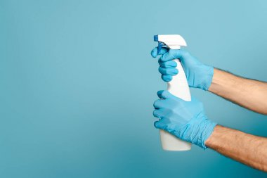 Cropped view of cleaner in rubber gloves holding spray detergent on blue background stock vector