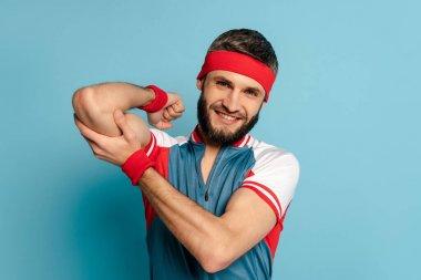 smiling stylish sportsman touching biceps on blue background
