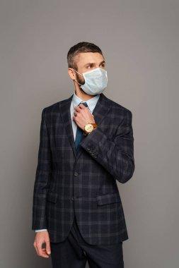 Handsome businessman in medical mask adjusting tie on grey background stock vector