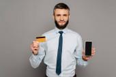 jóképű szakállas üzletember kezében hitelkártya és okostelefon üres képernyő szürke háttér