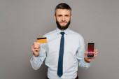 pohledný vousatý podnikatel držící kreditní kartu a smartphone s obchodní kurzy app na šedém pozadí