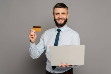 Smiling handsome bearded businessman with laptop and credit card on grey background stock vector