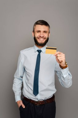 Smiling handsome bearded businessman with credit card on grey background stock vector