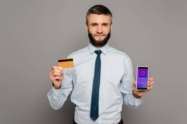 Handsome bearded businessman holding credit card and smartphone with online shopping app on grey background stock vector