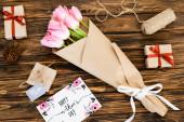 pohled shora na blahopřání se šťastnými nápisy dnů matek v blízkosti dárků a květin na dřevěném povrchu
