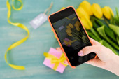 selective focus of woman taking photo of yellow tulips, gift box and mom tag lettering  on textured surface, mothers day concept