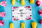horní pohled na kvetoucí žluté a růžové tulipány v blízkosti blahopřání se šťastnými matkami den nápis na modré