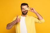 Lächelnder Mann bedeckt Auge mit Modell der Kreditkarte und zeigt Daumen-hoch-Geste auf gelbem Hintergrund